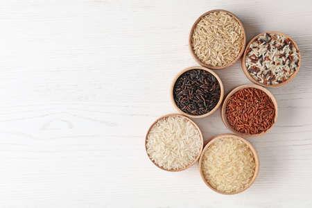 Platte lay compositie met bruine en andere soorten rijst in kommen op witte houten achtergrond. Ruimte voor tekst