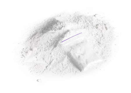 Pile of cocaine powder and bag on white background