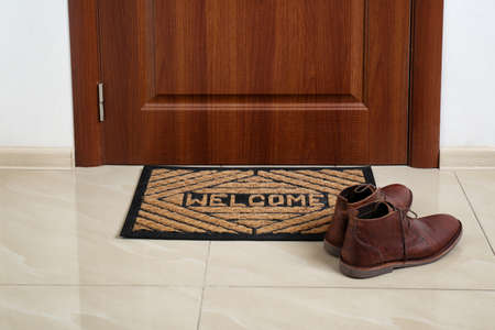 Brown classic shoes on welcome doormat in hall