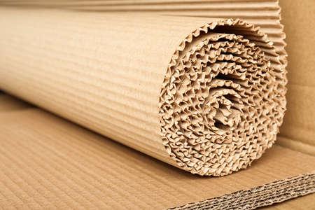 Rotolo di cartone ondulato marrone, primo piano. Materiale riciclabile
