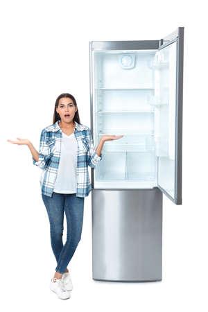Emotional woman near empty refrigerator on white background Фото со стока