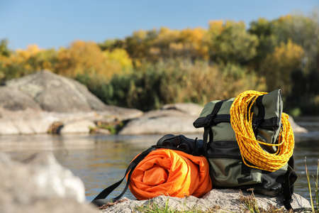 Set of camping equipment with sleeping bag on rock outdoors. Space for text