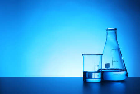 Chemistry laboratory glassware with samples on table against color background Banque d'images - 114028771