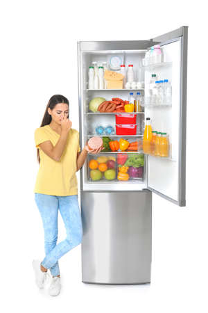 Young woman with expired sausage near open refrigerator on white background