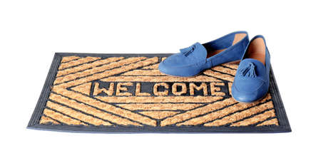 Blue female shoes on brown welcome doormat against white background
