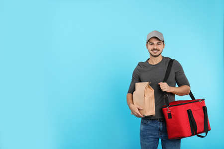 Young courier with thermo bag and paper package on color background, space for text. Food delivery service Stock Photo