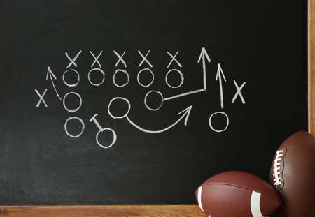 Rugby balls near chalkboard with football game scheme