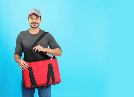 Young courier with thermo bag on color background, space for text. Food delivery service Stock Photo