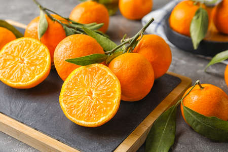 Board with ripe tangerines on table. Citrus fruit