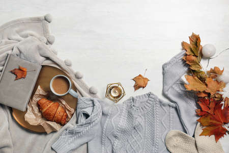 Flat lay composition with warm sweater and space for text on light background
