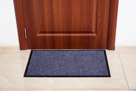 Modern welcome mat at door in hall