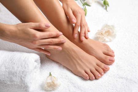 Mujer tocando sus pies suaves sobre una toalla blanca, primer plano. tratamiento de spa Foto de archivo
