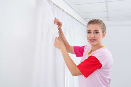 Woman hanging window curtain indoors. Interior decor element Stockfoto