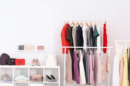 Racks with clothes in stylish dressing room interior