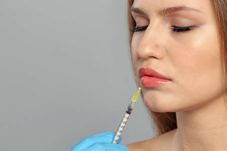 Young woman getting lips injection on grey background, space for text. Cosmetic surgery