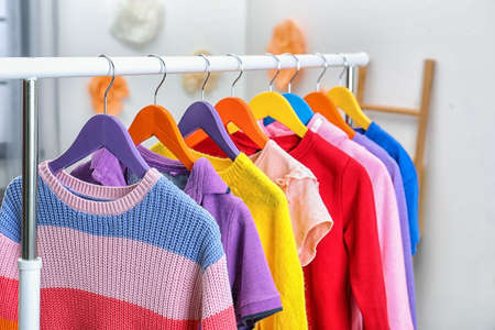 Colorful children's clothes hanging on wardrobe rack indoors, closeup Stockfoto