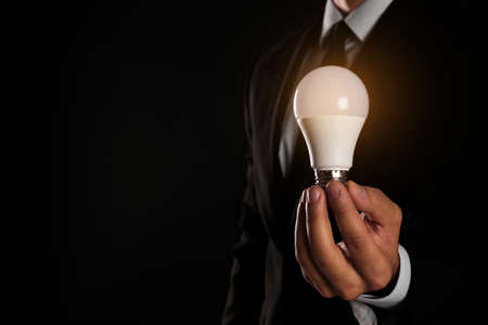 Businessman holding lamp bulb against dark background, closeup. Space for text