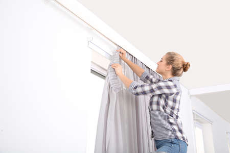 Woman hanging window curtain indoors. Interior decor element Banque d'images - 114190858