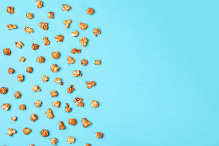 Flat lay composition with caramel popcorn and space for text on color background