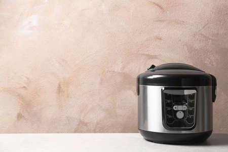 Modern multi cooker on table against color wall. Space for text