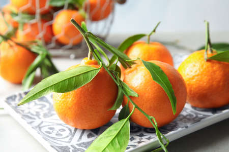 Plate with tasty ripe tangerines on table Standard-Bild