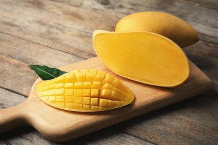 Ripe fresh mango on wooden board. Tropical fruit