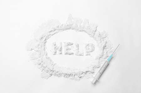 Word HELP written with cocaine and syringe on white background, top view