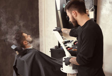 Hairdresser working with client at barbershop. Professional shaving service Banque d'images