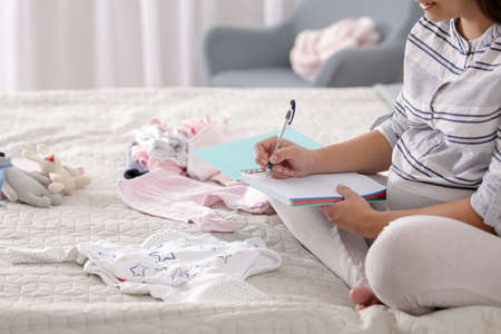 Pregnant woman writing packing list for maternity hospital on bed at home, closeup