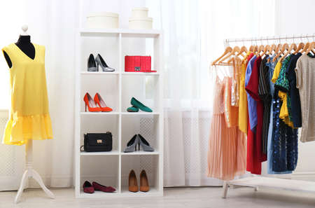 Shelving unit with shoes and purses in stylish dressing room interior Stock Photo