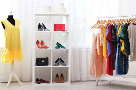 Unidad de estantería con zapatos y carteras en el elegante interior del vestidor Foto de archivo