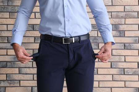 Businessman showing empty pockets near brick wall, closeup