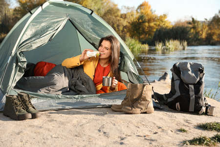 Young woman having breakfast in sleeping bag inside of camping tent
