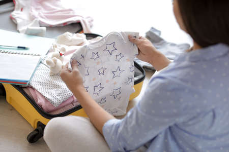 Pregnant woman packing suitcase for maternity hospital at home, closeup