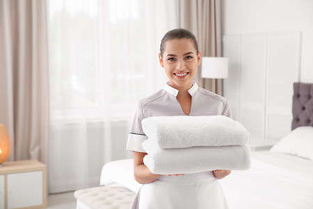 Young chambermaid with clean towels in bedroom Zdjęcie Seryjne