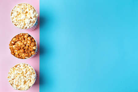 Different kinds of popcorn in paper cups on color background, top view. Space for text Stock Photo