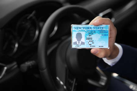 Man holding driving license in car, closeup. Space for text