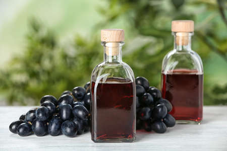 Bottles with wine vinegar and fresh grapes on wooden table against blurred background