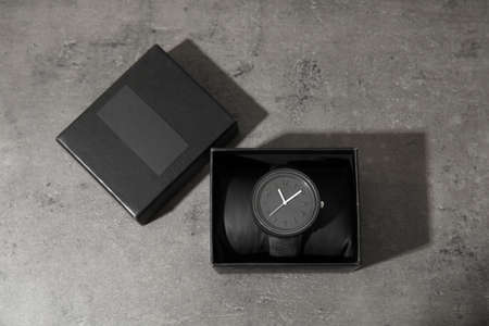Box with stylish wrist watch on gray background, top view. Fashion accessory