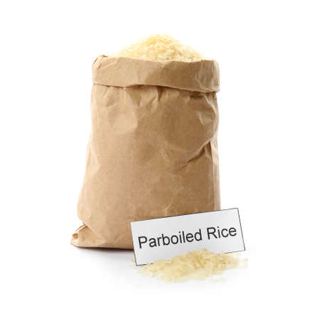 Paper bag with uncooked parboiled rice and card on white background 免版税图像