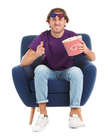 Emotional man with 3D glasses and popcorn sitting in armchair during cinema show on white background
