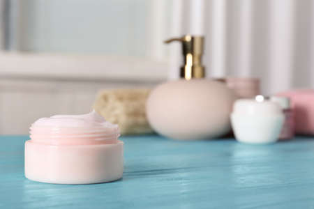Jar of body care product on table against blurred background. Space for text
