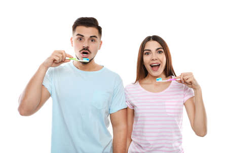 Happy couple brushing teeth on white background