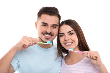 Happy couple brushing teeth on white background