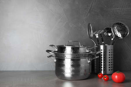 Set of clean cookware and utensils on table against grey background. Space for text