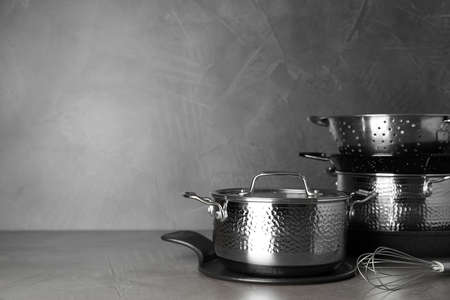 Set of clean cookware on table against grey background. Space for text