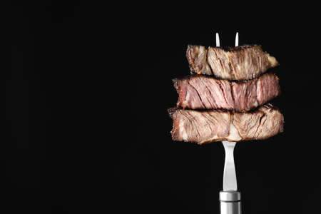 Fork with pieces of delicious barbecued meat on black background. Space for text