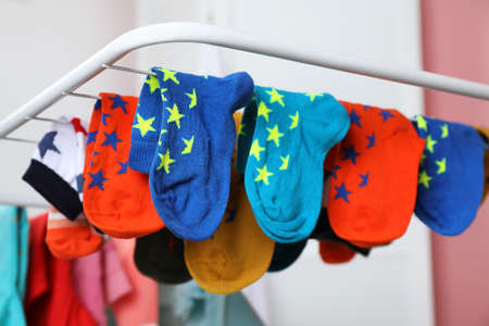 Different colorful socks on drying rack against blurred background, closeup