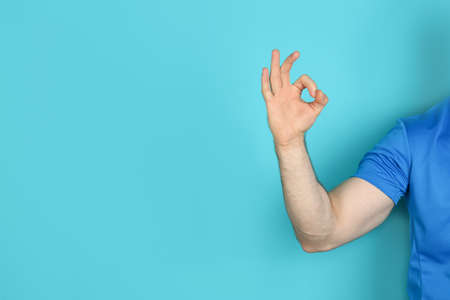 Young man showing OK gesture on color background. Space for text Reklamní fotografie