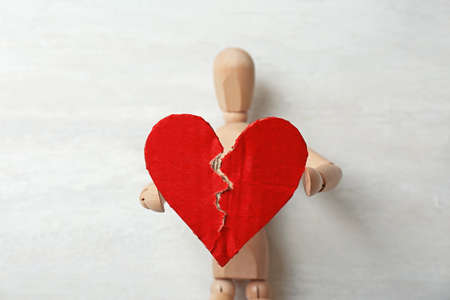 Wooden puppet with torn cardboard heart on gray background. Relationship problems